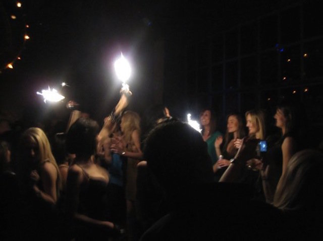 Bottle service maids holding flares to acknowledge a patron's purchase of bottle service