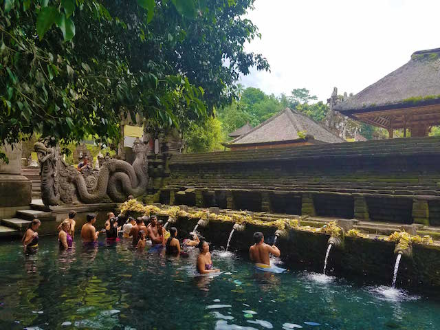 Tourists And Locals Taking A Bath At A Hindu Temple In Bali Indonesia.