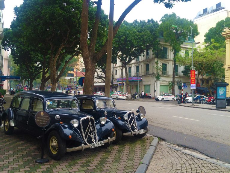 French Colonial Vehicles parked outside a hotel in Hanoi Vietnam.